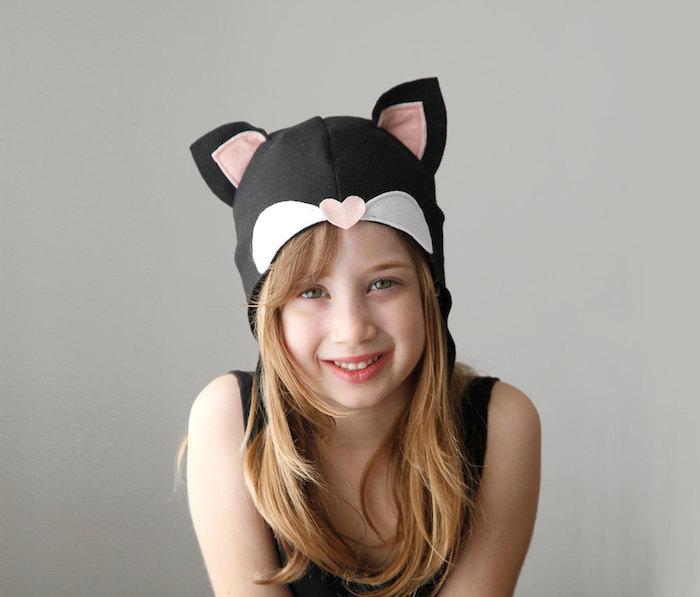 Halloween Masken wie eine schwarze Katze mit rosa Ohren und ein Herz als Nase
