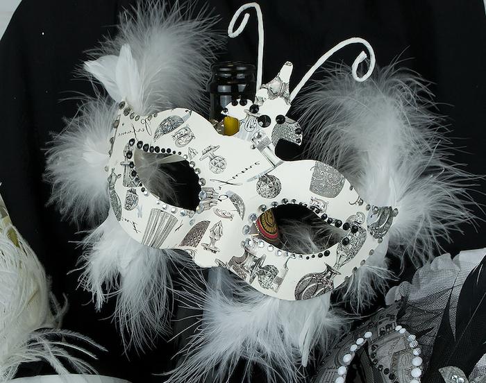weiße Halloween Masken, ein Schmetterling mit weißen Flügel mit Zeichnungen als Motive