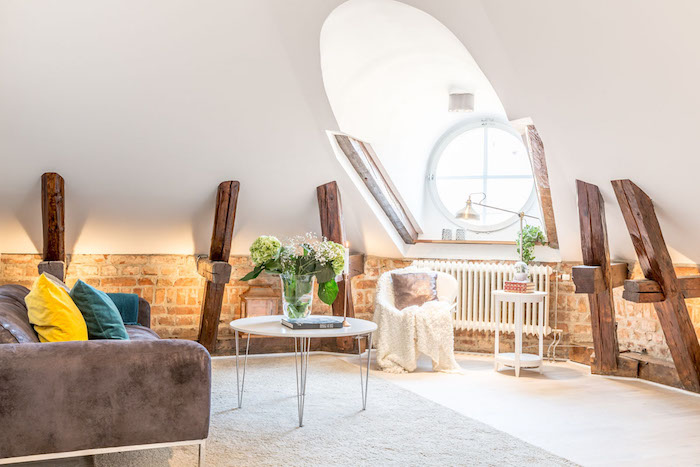dachschräge einrichten tolle idee dezent elegant stilvoll rundes fenster hölzerne elemente an den wänden sofa