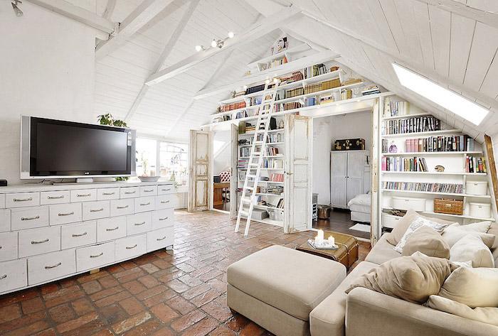 dachgeschosswohnung einrichtungsideen fernseher sofa beige kissen deko bücherregale bücher leiter treppe