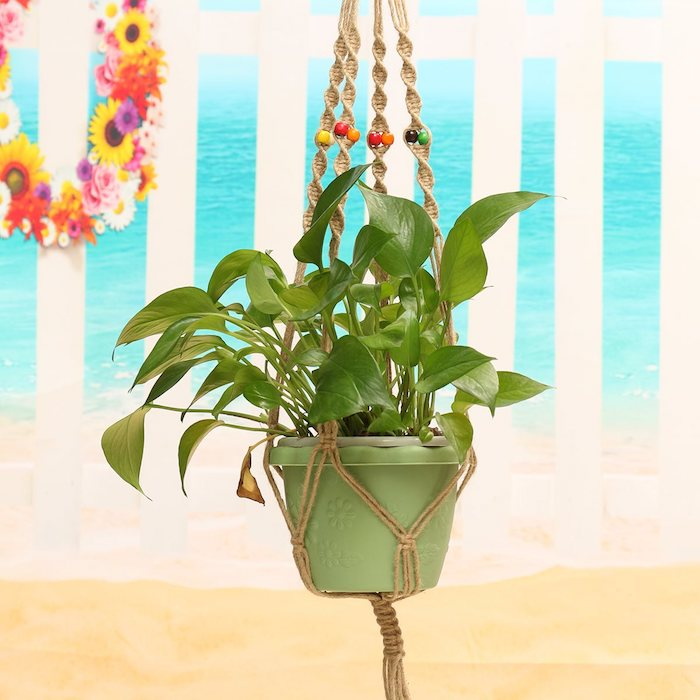armbänder knüpfen anleitung grüner blumentopf umgeben von bunten dekorationen und bunte perlen deko auf dem makramee hängeunterlage