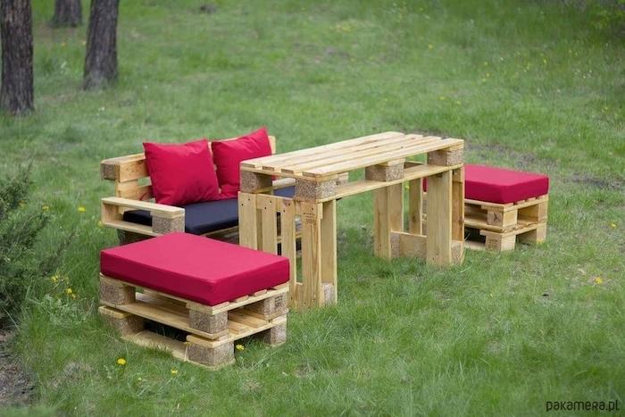 hier zeigen wir ihnen ein bild mit einer idee zum thema palettenmöbel für den garten - kleine sofas und tisch aus europaletten und mit kleinen roten kissen