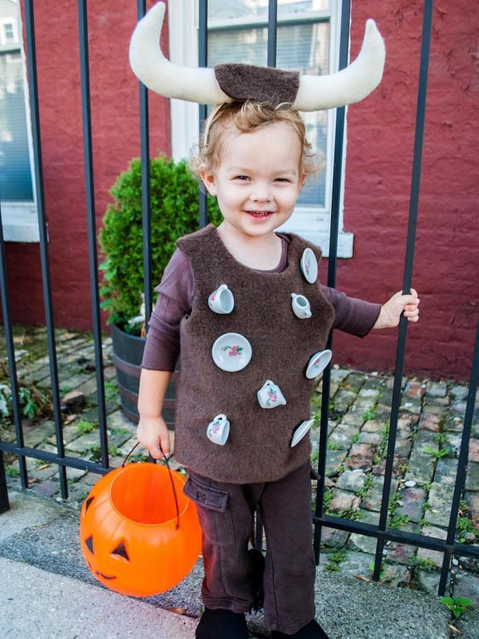 ein blonder Junge wie Stier gekleidet, kleine Tassen hängend - Halloween Kostüm Ideen für Kinder