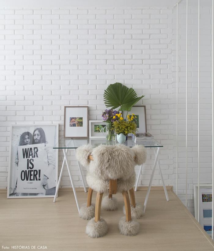 """Schreibtisch aus Glas, Holzstuhl mit Pelz bedeckt, Bilder und grüne Pflanzen, """"War is over"""", Beatles"""