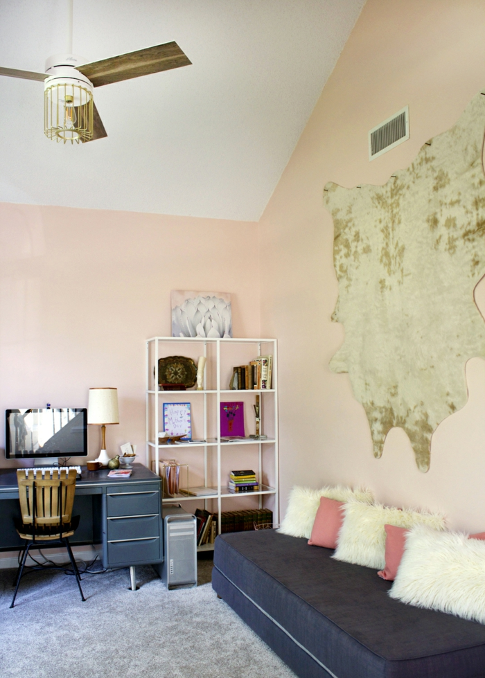 Arbeitszimmer in Pfirsich, Holzmöbel in Vintage, schwarzes Sofa, kleine Dekokissen, Pelz an der Wand