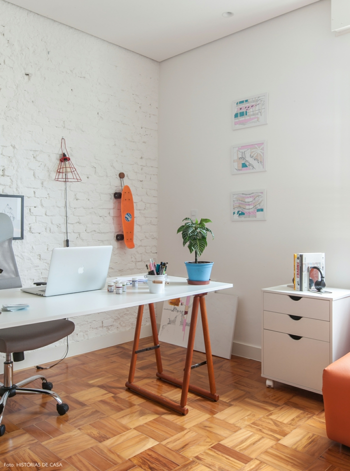 Arbeitszimmer in Weiß, Schreibzisch aus Holz, grauer Lederstuhl mit Rollen, Skateboard an der Wand