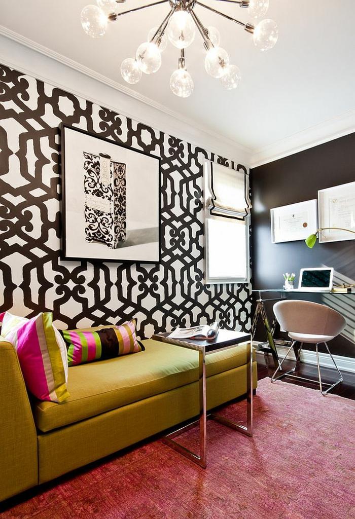 Arbeitszimmer und Wohnzimmer gleichzeitig, grünes Sofa, bunte Dekokissen, kleiner Schreibtisch, Magazin darauf, schwarzweiße Wände