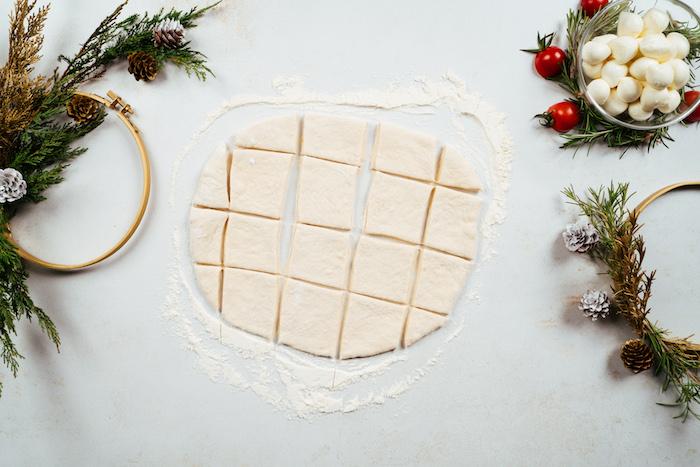 Pizzateig in gleich große Quadrate schneiden, Rezept für Brötchenkranz, Fingerfood für Weihnachten