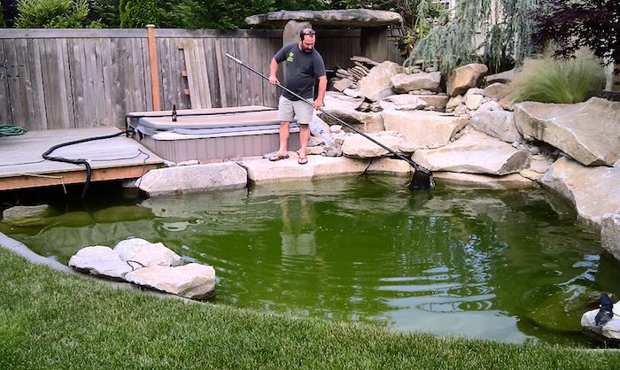 Gartenteich mit einem Kescher vom Laub reinigen, Holzboden, Schwimmbad
