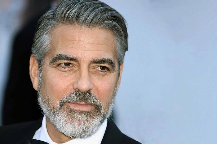 George Clooney mit Vollbart auf dem roten Teppich, weißes Hemd, schwarzer Anzug