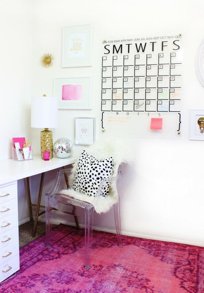 Arbeitszimmer in Weiß und Rosa, Kunststoffstuhl, Schreibtisch aus Holz, Kalender an der Wand, rosafarbener Teppich