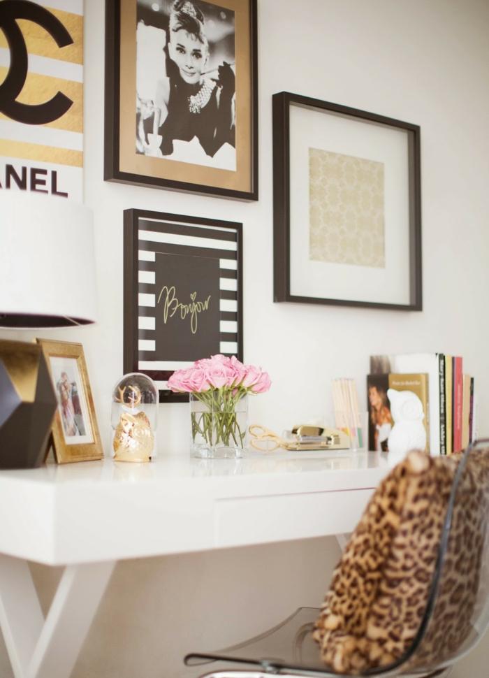 Arbeitszimmer Einrichtungsideen, weißer Schreibtisch aus Holz, durchsichtiger Kunststoffstuhl, Bilder an der Wand, kleiner Rosenstrauss, Bücher auf dem Tisch
