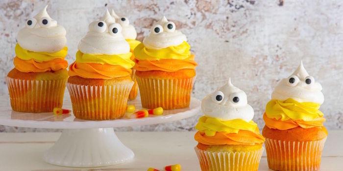 halloween backen, kleine dessers mit kürbis dekoriert mit oranger, gelber und weißer sahne