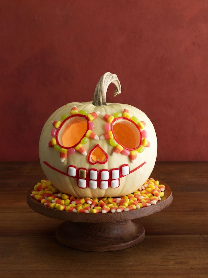 Die Augen von Kürbis schnitzen und mit Süßigkeiten dekorieren auf einem Tisch