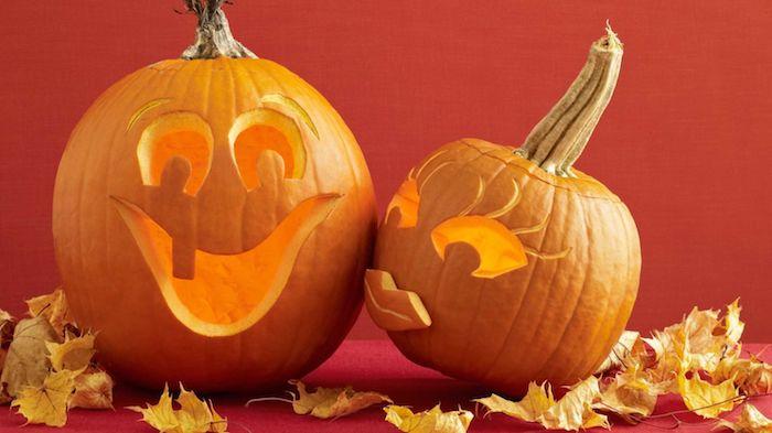zwei Kürbisse wie ein Ehepaar, das sich küsst - Halloween Bilder mit Laub dekoriert