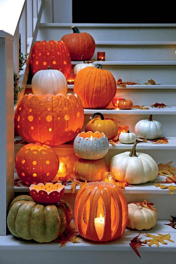 kleine und große Kürbisse mit Löcher auf der Treppe geordnet - Bastelideen Halloween
