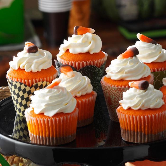 halloween gebäck, cupcakes in orange und braun dekoriert mit sahne und geleebonbons
