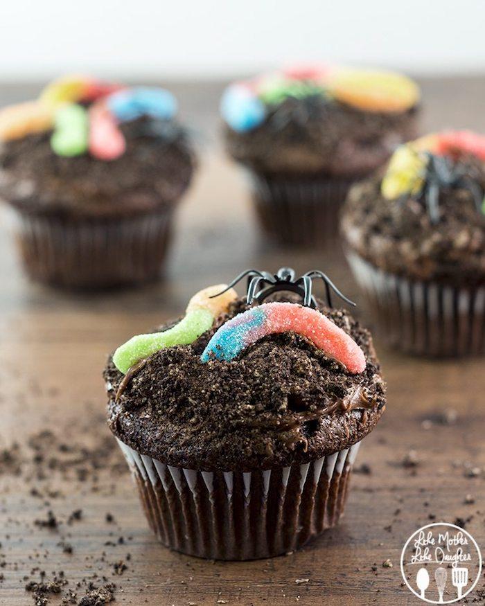 halloween gebäck, cupcakes dekoriert mit spinnen aus schokolade und gellebonbons