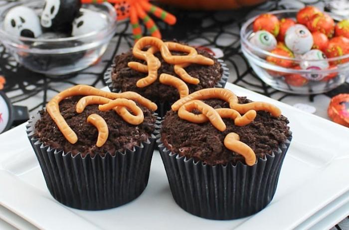 halloween gebäck, cupcakes mit wurmeln aus oranger buttercreme dekorieren