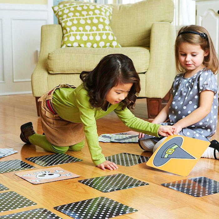 Halloween Spiele, zwei kleine Mädchen spielen mit Karten auf dem Boden im Wohnzimmer