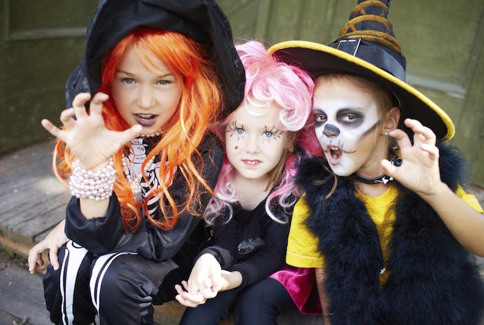 Halloween Kostüm für Kinder - zwei Mädchen und ein Junge wie Hexen verkleidet