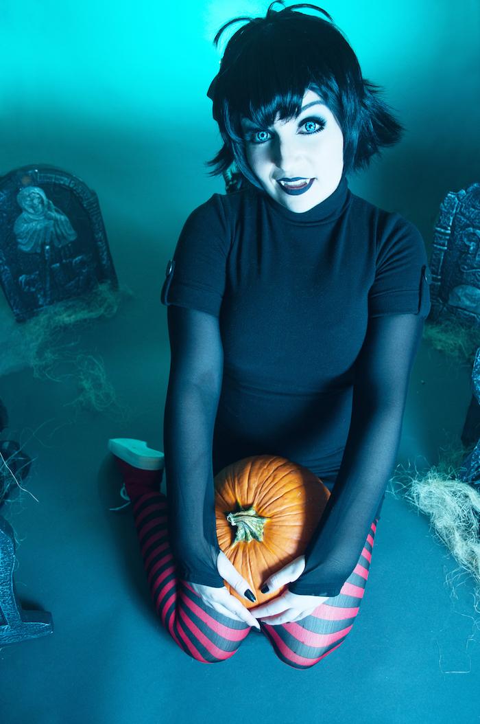 Ein Mädchen wie Vampire verkleidet mit einem Kürbis auf einem improvisierten Friedhof - einfache Kostüme