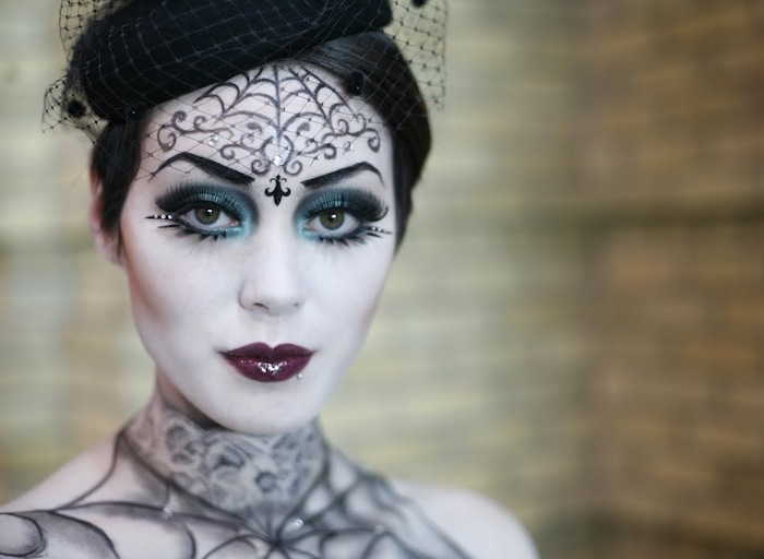 einfaches Kostüm von einer Frau, die sich als Spinne verkleidet hat - mit Hut, Make-up und passendes Kleid