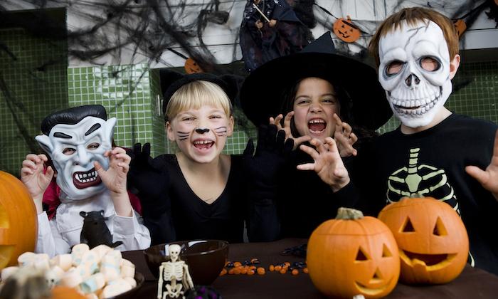 eine Gruppe von Kindern wie Vampir, schwarze Katze, Hexe und Skeleton maskiert - einfache Halloween Kostüme