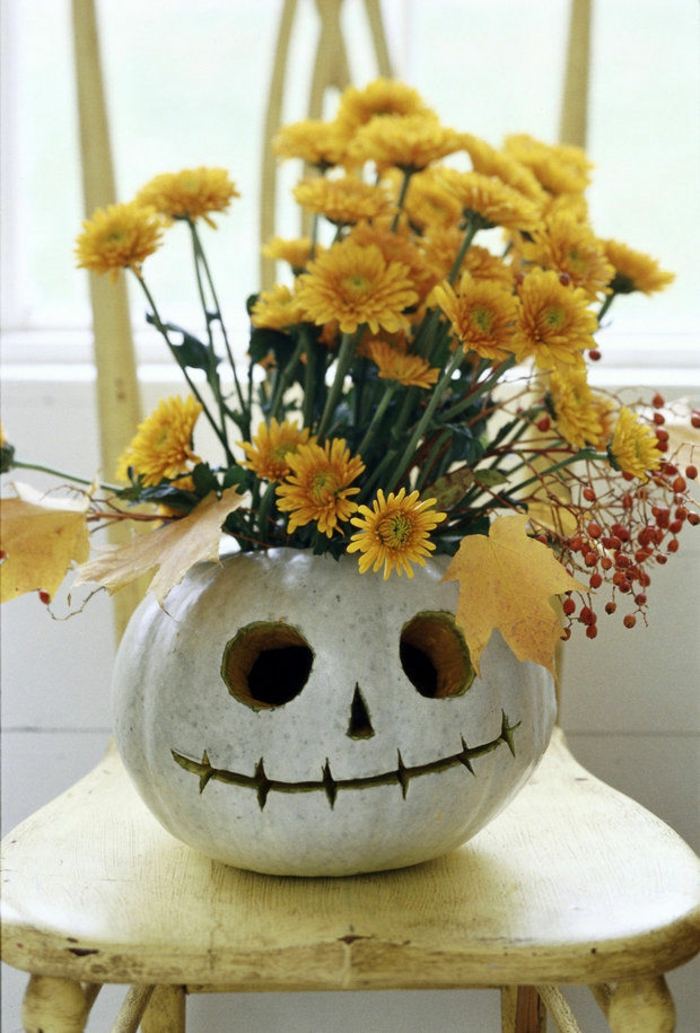 ein weißes Kürbisgesicht mit gelben Blumen und Blätter als Dekoration