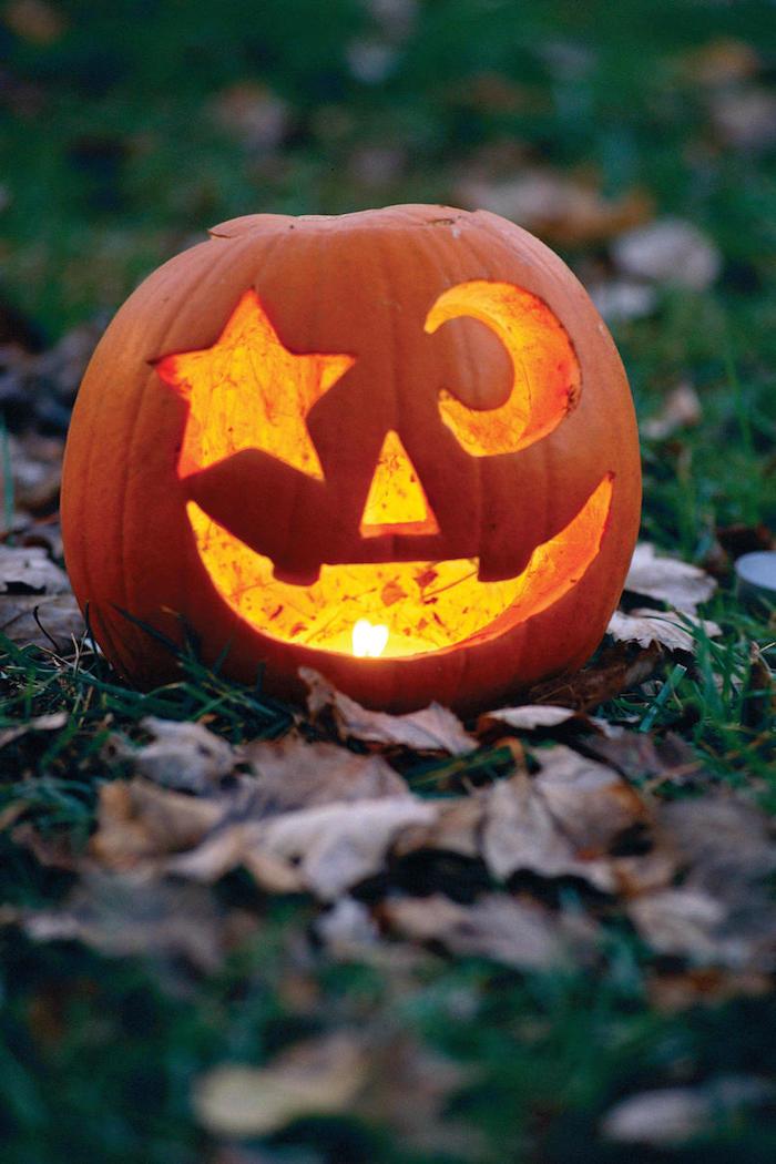 Halloween Bilder ein Kürbis auf Laub zwei Augen - ein Stern und ein Mond