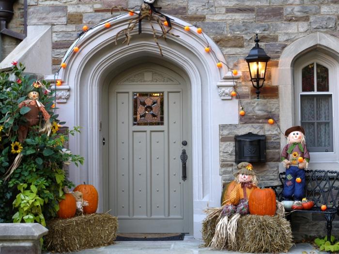 Eine Tür mit Lichterkette wie Kürbisse, Strohpuppen und Halloween Kürbisse