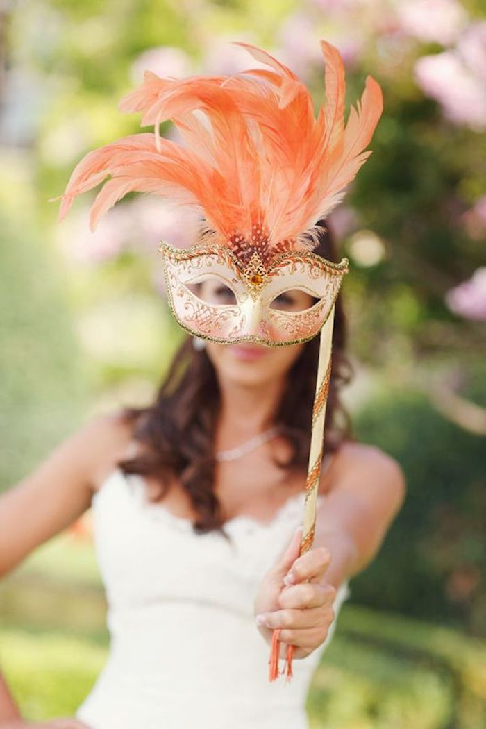 eine orange Halloween Maske mit ein paar orange Feder als Dekoration - Maske basteln