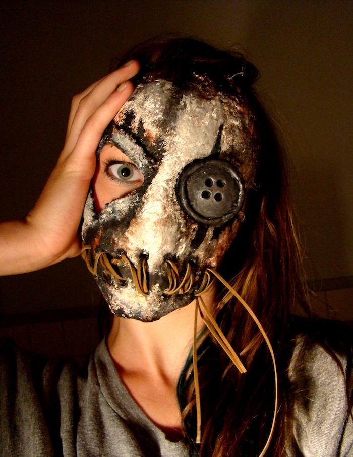 eine graue Maske ein Knopfauge und genähten Mund - gruselige Halloween Masken