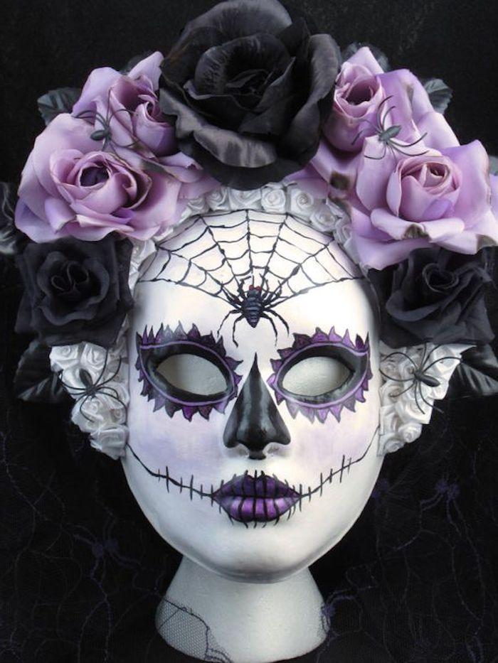 eine lila Maske mit einem Spinnennetz und lila und schwarze Blumen als Dekoration - gruselige Halloween Masken