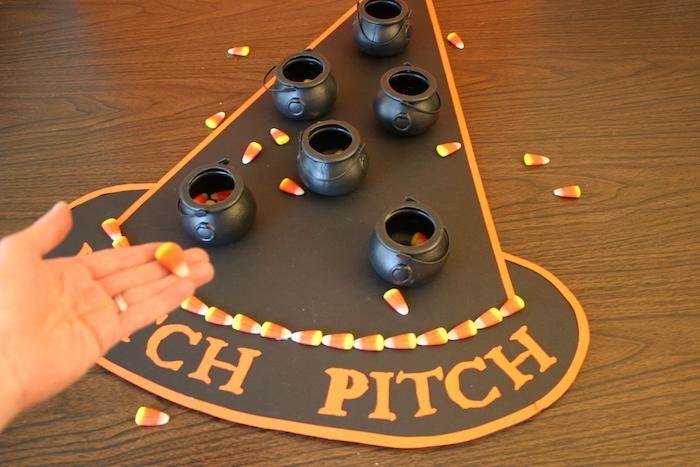 Kartonhut mit orangen Buchstaben, kleine Plastiktöpfe mit Gellee-Bonbons, Laminatboden