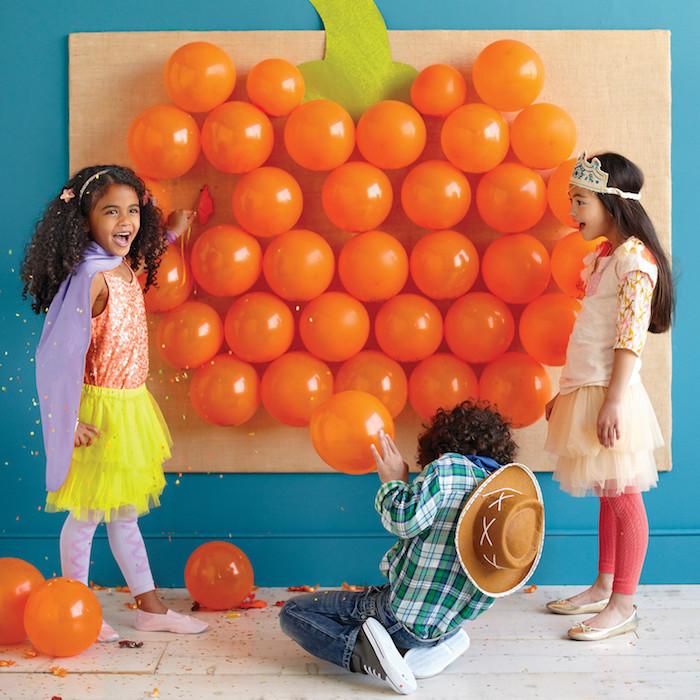 Halloween Spiele, Ballonspiel mit drei oder mehreren Spielern, weißer Holzboden, blaue Wand