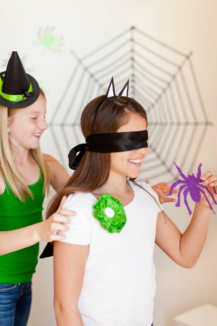 Spiel mit verbundenen Augen, die Spinne an der Wand kleben