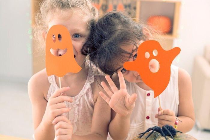 zwei Mädchen mit weißen Kleidern, Geister aus orangem Karton, Holzregal an der Wand
