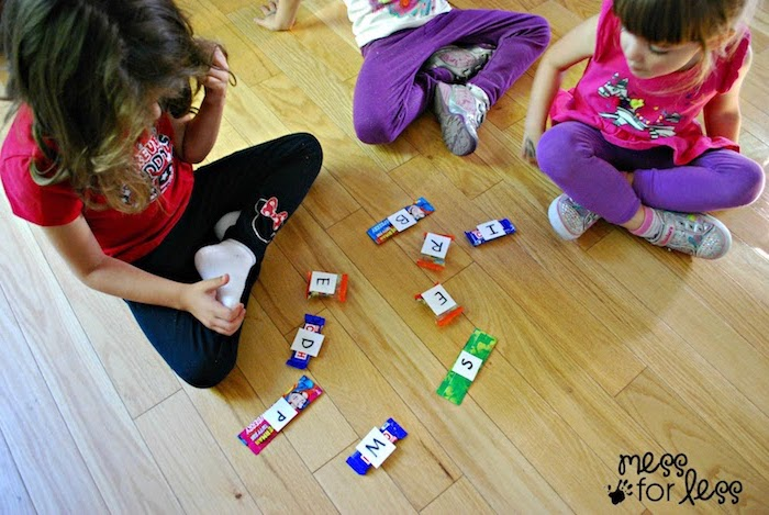 Kinder in Sportkleidung spielen Scrabble mit Kaugummis auf dem Boden
