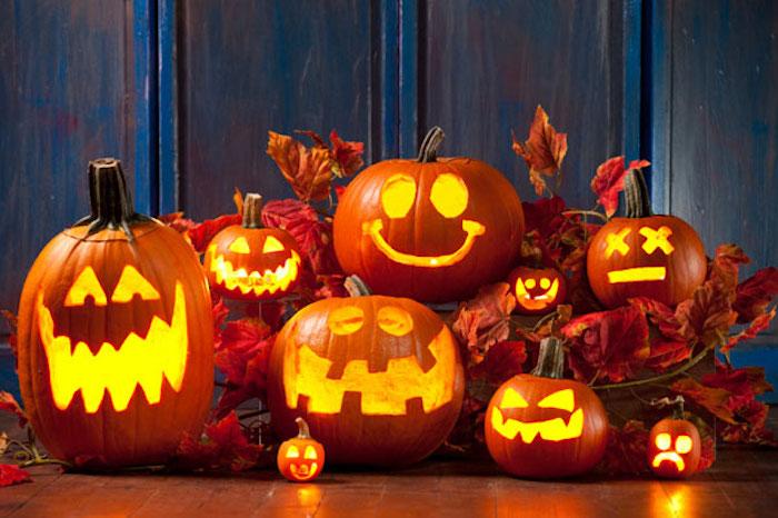 tolle Halloween Deko mit Kerzen und Kürbissen, buntes Laub, dunkelblaue Holzwand