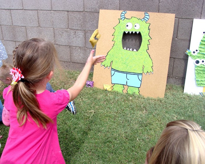 ein Junge krabbelt auf dem Gras, zwei dunkelblonden Mädchen spielen zusammen