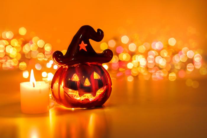 eine Figur aus Glas neben einer Kerze und glänzende Lichter im Hintergrund - Halloween Hintergrund