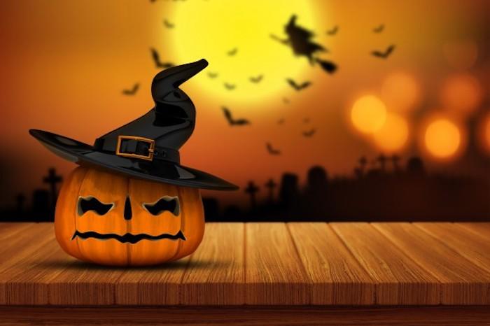 ein Kürbis mit Hexenhut - Halloween Hintergrund mit vielen Silhouetten