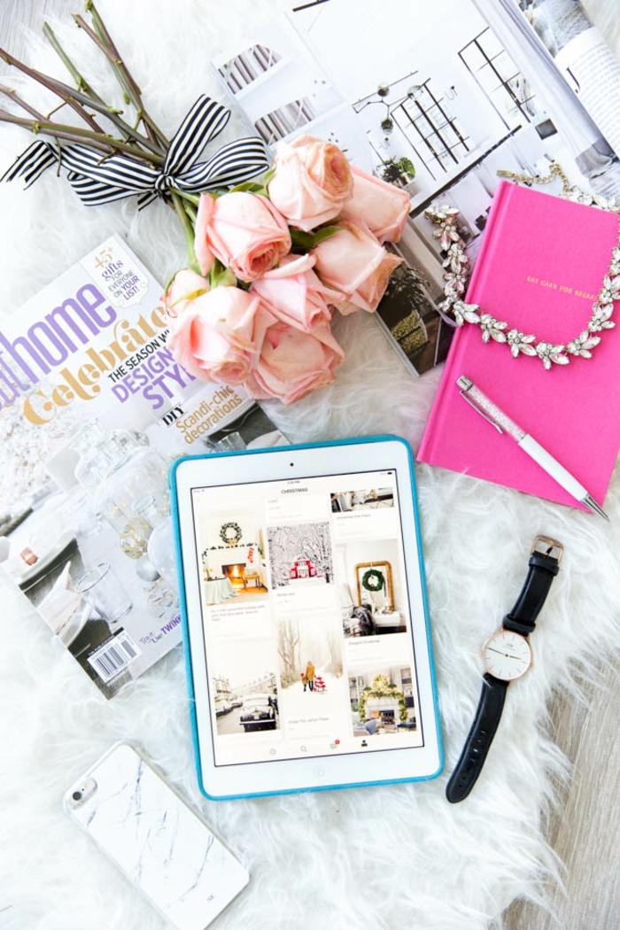 Blumenstrauss, verziert mit Bändchen, zwei Magazine, Kette mit Kristallen, Swarovski Kugelschreiber, Handuhr, Handy und Tablett