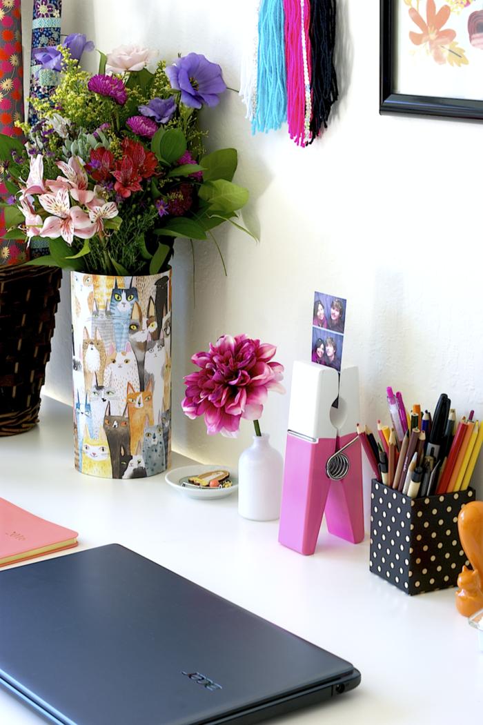 weißer Schreibtisch, Vase mit Katzen, Stifthalter mit vielen Kugelschreibern und Bleistiften, große Chrysantheme, Laptop und Fotohalter