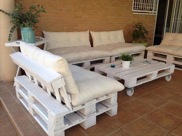 hier finden sie eine ganz tolle idee zum thema palettenmöbel terrasse - hier sind drei weiße sofas und ein weißer kleiner tisch aus weißen paletten und weiße große kissen