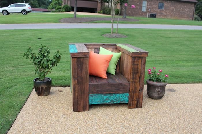 hier ist ein sessel aus holz und mit kleinen orangen und grünen kissen - tolle idee zum thema gartenmöbel aus paletten