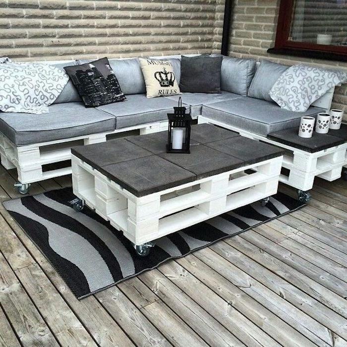 hier finden sie zwei sofas aus alten europaletten und mit großen und grauen kissen und einen weißen kleinen tisch - tolle idee zum thema palettenmöbel terrasse