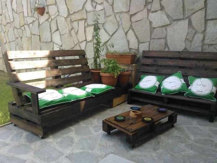 hier finden sie nnoch einige einzigartige selbstgebaute palettenmöbel - sofas mit kleinen grünen kissen und ein kleiner tisch aus europaletten