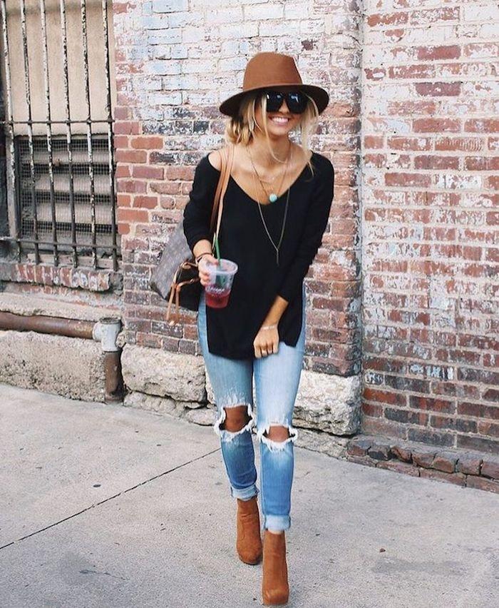 hippie kleider, frau mit jeans, schwarze bluse und braunem hut